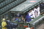Chicago Cubs players look to the field from the dugout during a rain delay in the ninth inning of a baseball game against the Pittsburgh Pirates in Chicago, Sunday, Aug. 2, 2020. (AP Photo/Nam Y. Huh)