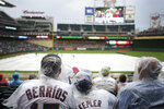 Minnesota Twins fans watch from under plastic rain ponchos as a Jimmy Buffet cover band entertains the crowd during a rain delay Friday, July 5, 2019, before a baseball game between the Texas Rangers and the Twins in Minneapolis. (Anthony Souffle/Star Tribune via AP)