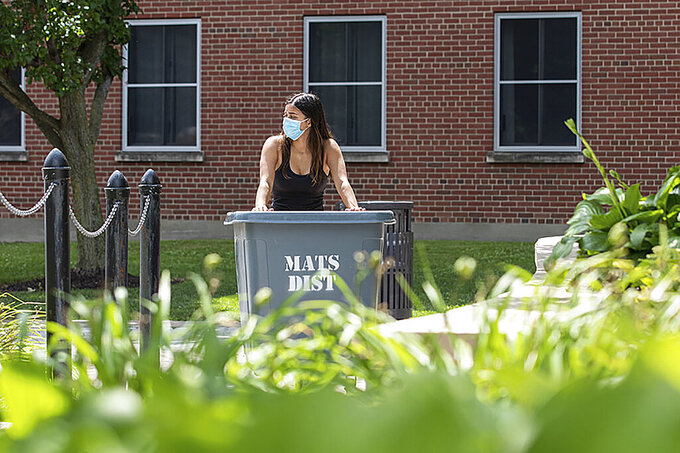 In this photo provided by Marilyn Hesler and Syracuse University, a student wearing a mask wheels her belongings up a ramp to move into her dorm, Sunday, Aug. 2, 2020, at Syracuse University in Syracuse, N.Y. (Marilyn Hesler/Syracuse University via AP)
