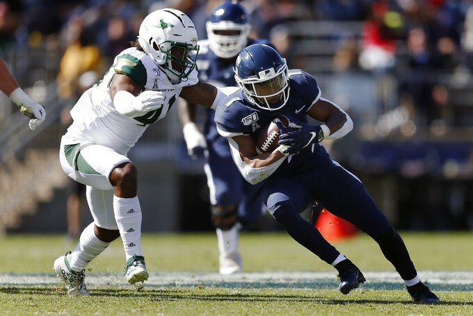 Connecticut running back Art Thompkins, right, carries against South Florida linebacker Demaurez Bellamy (41) during the first half of an NCAA college football game in East Hartford, Conn., Saturday, Oct. 5, 2019. (AP Photo/Michael Dwyer)