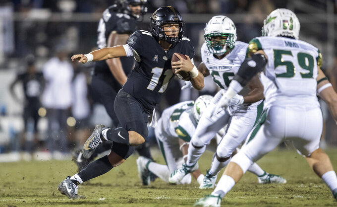 Central Florida quarterback Dillon Gabriel (11) sprints away from the South Florida defense during the second half of an NCAA college football game Friday, Nov. 29, 2019, in Orlando, Fla. (AP Photo/Willie J. Allen Jr.)
