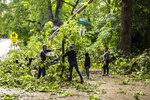 Residents help clear a fallen tree from an intersection after a severe storm, Monday, Aug. 10, 2020, in Iowa City, Iowa. (Joseph Cress/Iowa City Press-Citizen via AP)