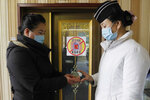 """FILE - In this Feb. 5, 2021, file photo, a staff member, right, of the Pongnam Noodle House disinfects the hands of a woman coming into its restaurant in Pyongyang, North Korea. Isolated North Korea has continued to claim a perfect record in keeping out the coronavirus in its latest report to the World Health Organization, on Wednesday, April 7, 2021. At the beginning of the pandemic more than a year ago, North Korea shut its borders and described its efforts to keep out the virus as a """"matter of national existence."""" It banned tourists, jetted out diplomats and still severely limits cross-border traffic while quarantining tens of thousands of people who have shown symptoms. (AP Photo/Jon Chol Jin, File)"""