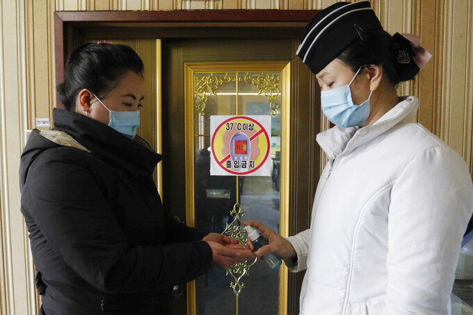 "FILE - In this Feb. 5, 2021, file photo, a staff member, right, of the Pongnam Noodle House disinfects the hands of a woman coming into its restaurant in Pyongyang, North Korea. Isolated North Korea has continued to claim a perfect record in keeping out the coronavirus in its latest report to the World Health Organization, on Wednesday, April 7, 2021. At the beginning of the pandemic more than a year ago, North Korea shut its borders and described its efforts to keep out the virus as a ""matter of national existence."" It banned tourists, jetted out diplomats and still severely limits cross-border traffic while quarantining tens of thousands of people who have shown symptoms. (AP Photo/Jon Chol Jin, File)"