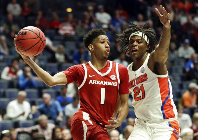 Arkansas guard Isaiah Joe (1) passes around Florida forward Dontay Bassett (21) in the first half of an NCAA college basketball game at the Southeastern Conference tournament Thursday, March 14, 2019, in Nashville, Tenn. (AP Photo/Mark Humphrey)