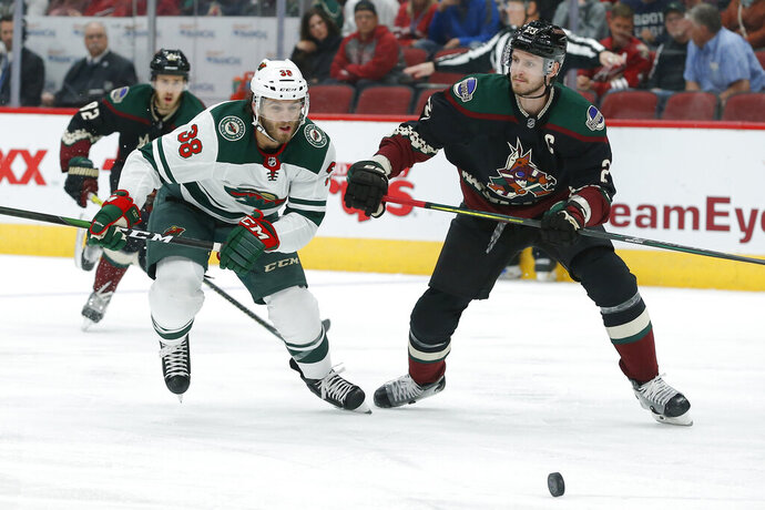 Minnesota Wild right wing Ryan Hartman (38) and Arizona Coyotes defenseman Oliver Ekman-Larsson chase the puck in the first period during an NHL hockey game, Saturday, Nov. 9, 2019, in Glendale, Ariz. (AP Photo/Rick Scuteri)