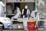 In this Tuesday, June 16, 2020, photo, Washington National Guard medics wear full protective equipment as they prepare to test a driver at a coronavirus test site in Yakima, Wash. Yakima, Benton and Franklin counties remain in Phase 1, meaning only essential businesses are open; restaurant service is limited to takeout and delivery; and limited outdoor recreation. (AP Photo/Elaine Thompson)