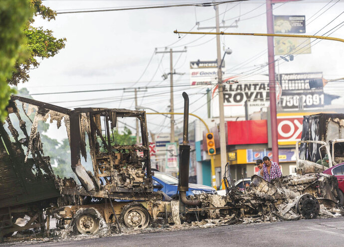 A burnt out semi truck used by gunmen smolders on an intersection, a day after street battles between gunmen and security forces in Culiacan, Mexico, Friday Oct. 18, 2019. Mexican security forces backed off an attempt to capture a son of imprisoned drug lord Joaquin