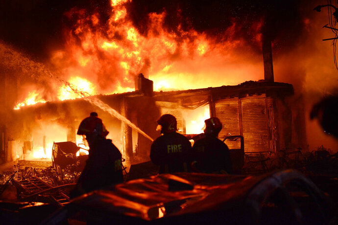 In this Wednesday, Feb. 20, 2019, photo, firefighters try to douse a fire in Dhaka, Bangladesh. A devastating fire raced through at least five buildings in an old part of Bangladesh's capital and killed scores of people. (AP Photo/Mahmud Hossain Opu)