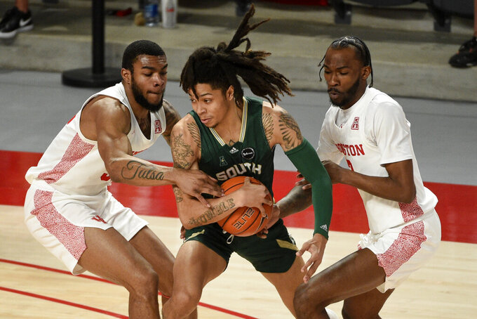 South Florida guard Caleb Murphy, center, looks to pass as Houston forward Reggie Chaney, left, and guard DeJon Jarreau defend during the first half of an NCAA college basketball game, Sunday, Feb. 28, 2021, in Houston. (AP Photo/Eric Christian Smith)