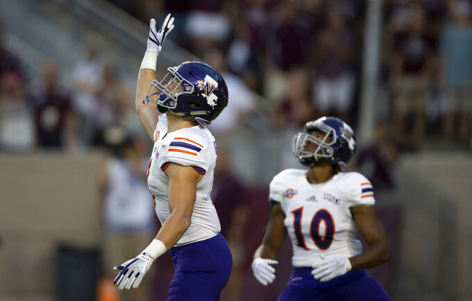 FILE - In this Aug. 30, 2018, file photo, Northwestern State's Ryan Reed (8) waves for a fair catch on the opening kickoff against Texas A&M during an NCAA college football game in College Station, Texas. Kickoff returns are down about 20 percent in the first year of a new NCAA rule that gives the receiving team possession at its 25-yard line if the kick is fair caught anywhere between the goal line and 25. (AP Photo/Sam Craft, File)