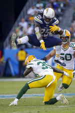 Los Angeles Chargers running back Melvin Gordon jumps over Green Bay Packers defensive back Chandon Sullivan during the second half of an NFL football game Sunday, Nov. 3, 2019, in Carson, Calif. (AP Photo/Marcio Jose Sanchez)