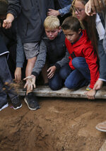 A child tosses a handful of dirt on the coffin that contains the remains of 12-year-old Howard Jacob Miller Jr., at the cemetery in Colonia Le Baron, Mexico, Friday, Nov. 8, 2019, during a burial service for Rhonita Miller and four of her young children. The bodies of Miller and four of her children were taken in a convoy of pickup trucks and SUVS, on the same dirt-and-rock mountainous road where they were killed Monday by drug cartel men, for burial in the community of Colonia Le Baron in Chihuahua state. (AP Photo/Marco Ugarte)