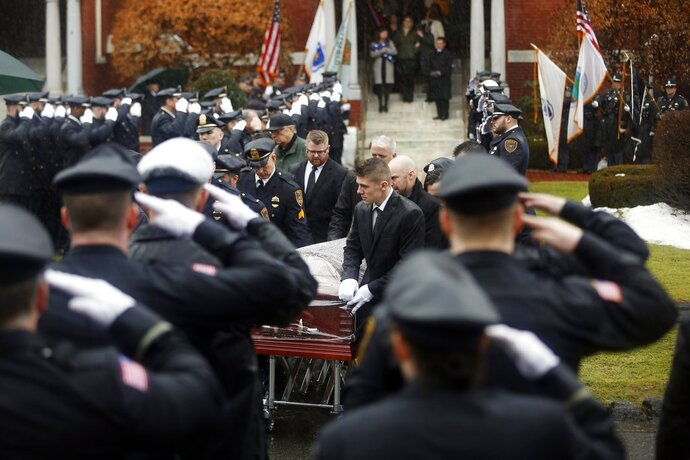 Andrew Winston, center, acts as pallbearer for the casket of his father, Pittsfield Fire Lt. Michael Winston, as first responders and  community members gather at St. Charles Church, Friday, Jan. 12, 2018, in Pittsfield, Mass. Winston passed away suddenly on Jan. 5 while on vacation in Ft. Myers, Fla. (Stephanie Zollshan/The Berkshire Eagle via AP)