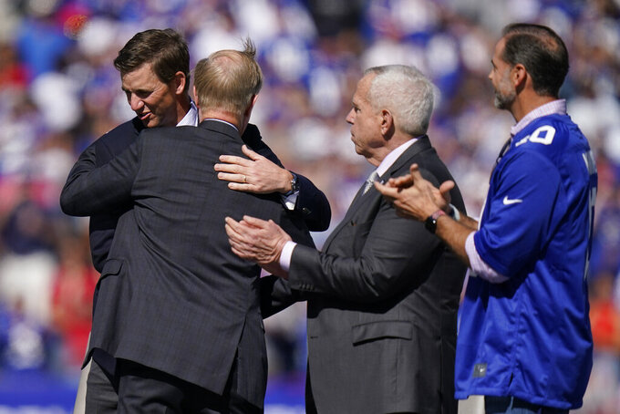 Former New York Giants quarterback Eli Manning, left, is hugged by team president John Mara, center left, during a ceremony to retire Manning's jersey number 10 and honor his tenure with the team during half-time in an NFL football game against the Atlanta Falcons, Sunday, Sept. 26, 2021, in East Rutherford, N.J. (AP Photo/Seth Wenig)
