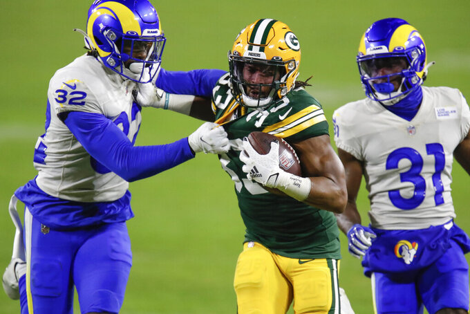 File-This Jan. 16, 2021, file photo shows Green Bay Packers' Aaron Jones (33) being chased down by Los Angeles Rams' Jordan Fuller (32) and Rams' Darious Williams during the second half of an NFL divisional playoff football game in Green Bay, Wis. The Pro Bowl running back, Jones has agreed to a new deal with the Green Bay Packers and won't be exploring free agency. Drew Rosenhaus, Jones' agent, confirmed that his client had agreed on a four-year deal worth $48 million that includes a $13 million signing bonus. (AP Photo/Matt Ludtke, File)