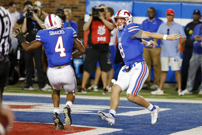 SMU running back Tre Siggers (4) celebrates with quarterback Tanner Mordecai (8) after Mordecai scored a rushing touchdown against Tulane during the first half of an NCAA college football game in Dallas, Thursday, Oct. 21, 2021. (AP Photo/Michael Ainsworth)