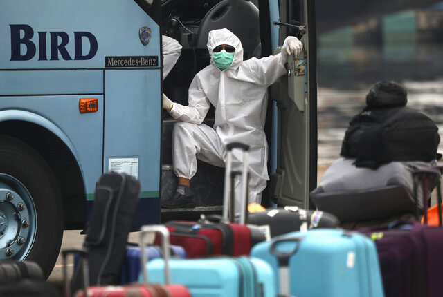 A bus crew member in protective gear waits near baggage from the Carnival Splendor cruise ship after it arrived at Tanjung Priok Port in Jakarta, Indonesia, Thursday, April 30, 2020. Hundreds of Indonesians working on the cruise ship were tested for the coronavirus and will be quarantined for 14 days due to the global pandemic. (AP Photo/Dita Alangkara)