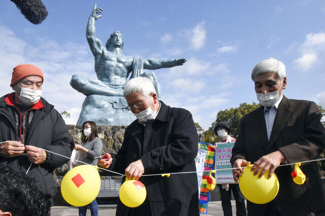 Participants deflate balloons in hope of neutralizing and demolishing nuclear warheads, during a memorial gathering at Peace Park in Nagasaki, southern Japan Friday, Jan. 22, 2021. The first-ever treaty to ban nuclear weapons entered into force on Friday, hailed as a historic step to rid the world of its deadliest weapons but strongly opposed by the world's nuclear-armed nations. (Kyodo News via AP)