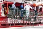 Migrants disembark from the humanitarian rescue ship Ocean Viking after it docked at the port of Pozzallo, in Sicily, southern Italy, Wednesday, Oct. 30, 2019. The migrants were rescued off Libya on Oct. 18, and the ship has been stranded despite an EU fast-track plan designed to resolve such cases. (Francesco Ruta/ANSA via AP)