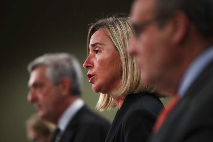 European Union Foreign Policy chief Federica Mogherini, center, talks to journalists during a joint news conference with UN High Commissioner for Refugees Filipo Grandi, left, and UN Migration Agency Director General Antonio Vitorino at the EU headquarters in Brussels, Tuesday, Oct. 29, 2019. The European Union says a