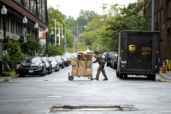 "In this May 22, 2020, photo, a delivery man pushes a cart full of packages to deliver to an apartment building on an almost empty street in the Shaw neighborhood of Washington. As a candidate for the White House, President Donald Trump once said he wanted ""whatever is best"" for the residents of the nation's capital. But over the course of his more than three years in office a disconnect between the president and District of Columbia has emerged -- a chasm that has only grown during the coronavirus pandemic. (AP Photo/Andrew Harnik)"