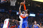 Detroit Pistons guard Bruce Brown, top left, shoots as Oklahoma City Thunder center Steven Adams defends during the first half of an NBA basketball game Friday, Feb. 7, 2020, in Oklahoma City. (AP Photo/Sue Ogrocki)