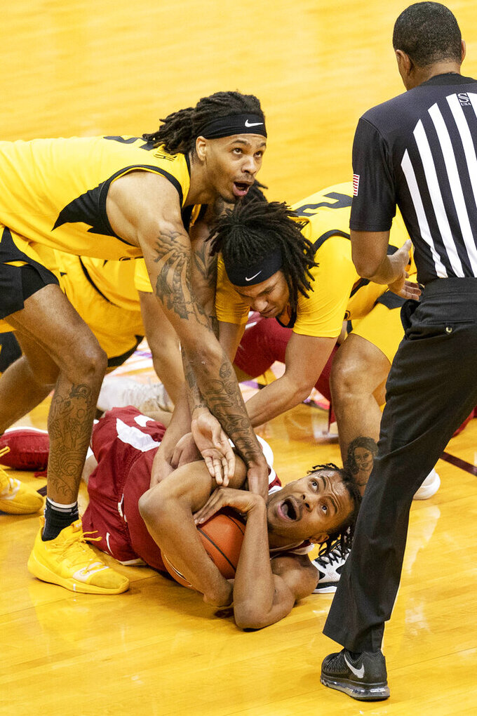 Arkansas' Moses Moody, bottom, tries to hold on to the ball as Missouri's Mitchell Smith, top, and Dru Smith, right, swarm him during the second half of an NCAA college basketball game Saturday, Feb. 13, 2021, in Columbia, Mo. (AP Photo/L.G. Patterson)