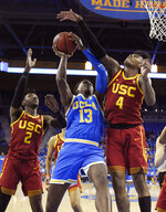 UCLA guard Kris Wilkes, center, shoots as Southern California guard Jonah Mathews, left, and guard Kevin Porter Jr. defend during the first half of an NCAA college basketball game Thursday, Feb. 28, 2019, in Los Angeles. (AP Photo/Mark J. Terrill)