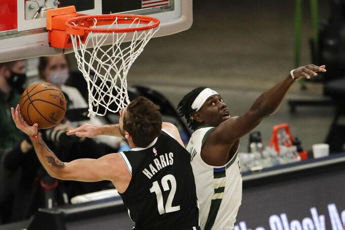 Brooklyn Nets' Joe Harris (12) shoots past Milwaukee Bucks' Jrue Holiday during the first half of an NBA basketball game Tuesday, May 4, 2021, in Milwaukee. (AP Photo/Aaron Gash)