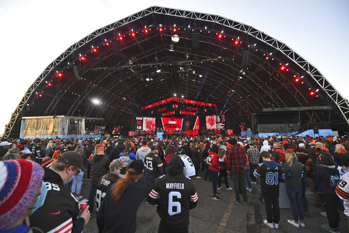 Fans watch the from the outside of the NFL Draft Theatre during the second round of the NFL football draft, Friday, April 30, 2021, in Cleveland. (AP Photo/David Dermer)
