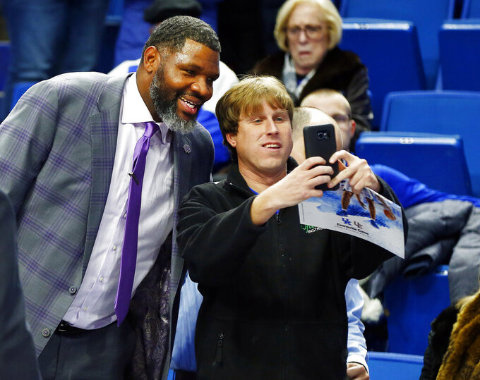 Evansville coach Walter McCarty, left, poses with a fan after Evansville defeated Kentucky 67-64 in an NCAA college basketball game in Lexington, Ky., Tuesday, Nov. 12, 2019. (AP Photo/James Crisp)