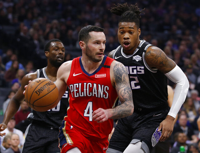 New Orleans Pelicans guard JJ Redick, left, drives against Sacramento Kings forward Richaun Holmes during the first quarter of an NBA basketball game in Sacramento, Calif., Saturday, Jan. 4, 2020. (AP Photo/Rich Pedroncelli)