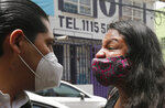 A young woman confronts an official of Mexico's governmental Human Rights Commission during a protest by a group of feminists who say the government has been slow to protect or support women who have suffered abuse or to help them in finding their missing loved ones, in Ecatepec, Mexico, Friday, Sept. 11, 2020. (AP Photo/Marco Ugarte)