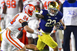 Notre Dame running back Kyren Williams (23) fends off Clemson Tigers safety Nolan Turner (24) on his way to a touchdown during the first quarter of an NCAA college football game Saturday, Nov. 7, 2020, in South Bend, Ind. (Matt Cashore/Pool Photo via AP)