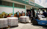 A worker moves goods with a forklift at the entrance of Mercabal wholesale market where customers wait to enter in Havana, Cuba, Thursday, July 30, 2020. The government is letting private businesses buy wholesale for the first time. (AP Photo/Ismael Francisco)