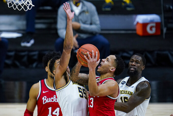 Ohio State guard CJ Walker (13) shoots over Michigan guard Eli Brooks (55) in the first half of an NCAA college basketball game at the Big Ten Conference tournament in Indianapolis, Saturday, March 13, 2021. (AP Photo/Michael Conroy)