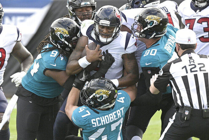 Houston Texans quarterback Deshaun Watson, center, is sacked by Jacksonville Jaguars defensive end Dawuane Smoot (94), linebacker Joe Schobert (47) and defensive tackle Taven Bryan (90) during the first half of an NFL football game, Sunday, Nov. 8, 2020, in Jacksonville, Fla. (AP Photo/Phelan M. Ebenhack)