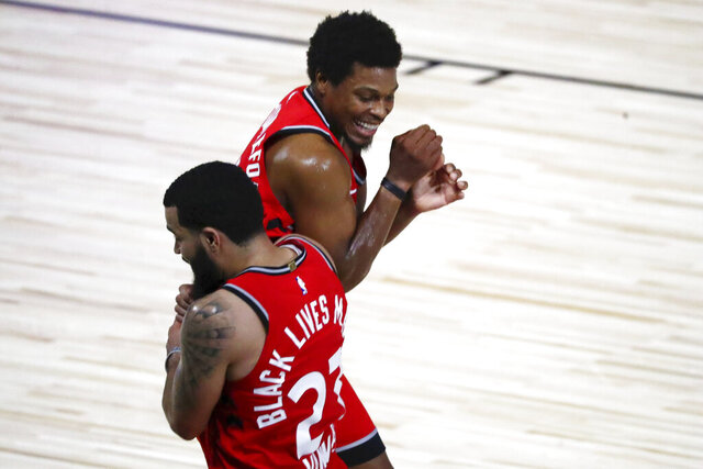 Toronto Raptors guard Fred VanVleet (23) celebrates with guard Kyle Lowry (7) after making a half court shot against the Brooklyn Nets to end the first half in Game 3 of an NBA basketball first-round playoff series, Friday, Aug. 21, 2020, in Lake Buena Vista, Fla. (Kim Klement/Pool Photo via AP)