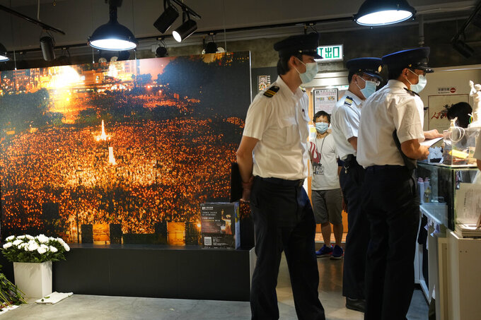 """Officers from Food and Environmental Hygiene Department ask questions to staff next to a huge photo of candlelight vigil at the """"June 4 Memorial Museum"""" run by The Hong Kong Alliance in Support of Patriotic Democratic Movements of China in Hong Kong Tuesday, June 1, 2021. The Hong Kong museum commemorating the bloody crackdown in Tiananmen Square in 1989 has been shut down days after its opening, as authorities continue to crack down on activities related to the event. The museum, which opened on Sunday and was meant to last until June 4, was closed on Wednesday by the organizers after authorities investigated the venue for not having the relevant licenses required for public exhibition. (AP Photo/Vincent Yu)"""