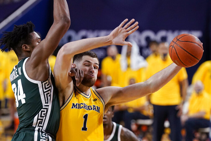Michigan center Hunter Dickinson (1) is fouled by Michigan State forward Julius Marble II (34) during the first half of an NCAA college basketball game Thursday, March 4, 2021, in Ann Arbor, Mich. (AP Photo/Carlos Osorio)