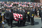 FILE - In this Aug. 20, 2018, file photo, the casket with fallen Utah firefighter Matthew Burchett is loaded into a fire engine after the funeral at the Maverik Center in West Valley City, Utah. Burchett, a firefighter battling the largest wildfire in California history, was killed last month when thousands of gallons of flame-suppressing liquid were dropped from a Boeing 747 that was mistakenly flying only 100 feet (30 meters) above the treetops, according to an official report Friday, Sept. 14. (Rick Egan/The Salt Lake Tribune via AP, File)