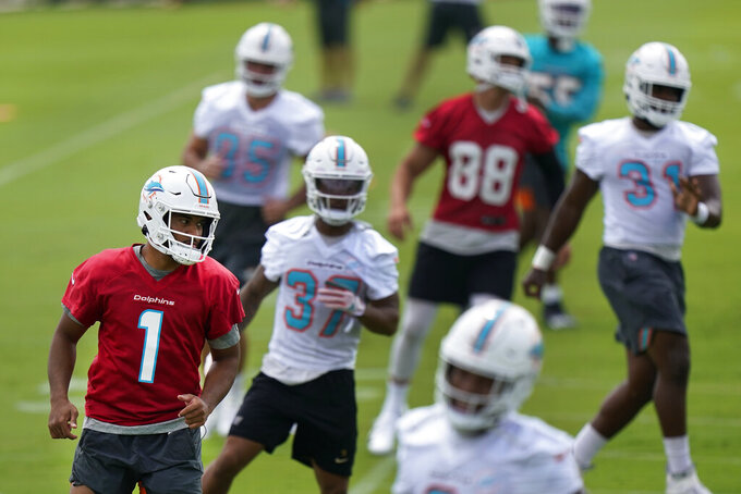 Miami Dolphins quarterback Tua Tagovailoa (1) warms up with teammates during a mandatory minicamp at the NFL football team's training camp, Tuesday, June 15, 2021, in Davie, Fla. (AP Photo/Wilfredo Lee)