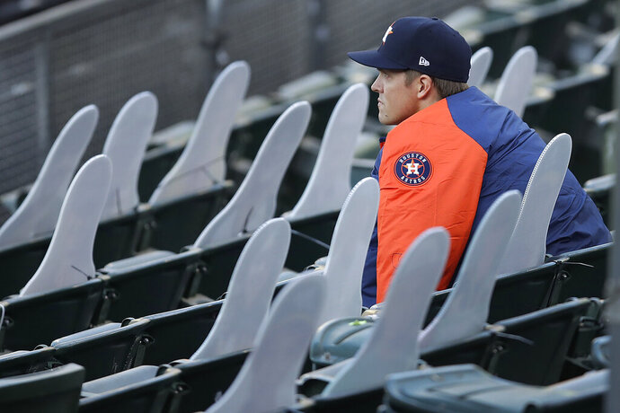 Houston Astros pitcher Zack Greinke socially distances himself beside cardboard cutout fans in the stands of the Oakland Coliseum in the fourth inning of a baseball game against the Oakland Athletics on Friday, Aug. 7, 2020, in Oakland, Calif. (AP Photo/Ben Margot)