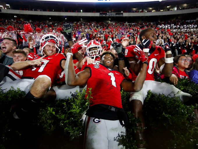 Georgia wide receiver George Pickens (1) celebrates with Eli Wolf, left, and J.R. Reed (20) after defeating Texas A&M 19-13 in an NCAA college football game Saturday, Nov. 23, 2019, in Athens, Ga. (AP Photo/John Bazemore)