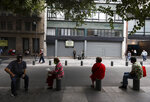 People keep their distance from each other to help curb the spread of the new coronavirus, at a street in Mexico, City, Wednesday, July 1, 2020. (AP Photo/Eduardo Verdugo)