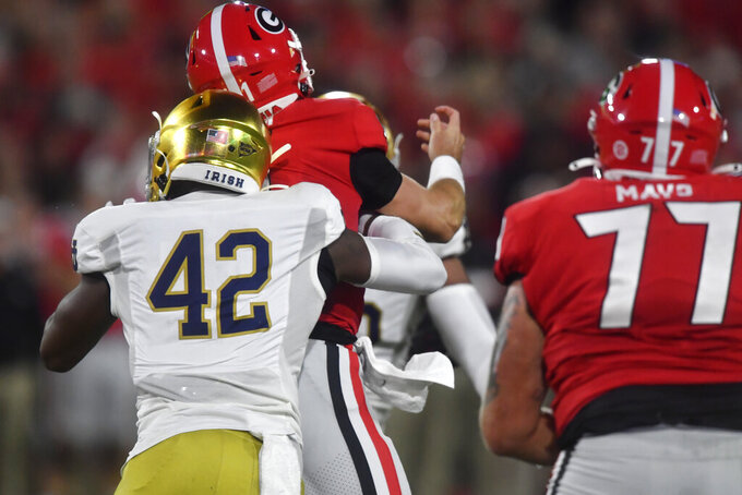 Notre Dame defensive lineman Julian Okwara (42) tacklaes Georgia quarterback Jake Fromm (11) during the first half of an NCAA college football game, Saturday, Sept. 21, 2019, in Athens, Ga. (AP Photo/Mike Stewart)