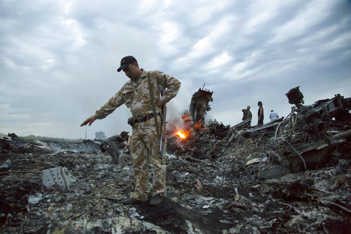FILE - In this July 17, 2014. file photo, people walk amongst the debris at the crash site of MH17 passenger plane near the village of Grabovo, Ukraine, that left 298 people killed. An international team of investigators piecing together a criminal case in the July 2014 shooting down Malaysia Airlines Flight 17 over eastern Ukraine said Thursday Nov. 14, 2019, that evidence suggests links between Russia and rebels in the region were closer than previously believed.(AP Photo/Dmitry Lovetsky, File)