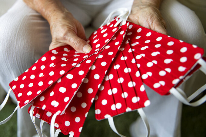 """Mae Krier, 95, of Levittown, Pa., an original """"Rosie the Riveter,"""" shows a handful of her polka dotted masks she's been making at her home in Levittown, Pa., on Wednesday, July 28, 2021. Krier spent her time building airplanes for Boeing during World War II which earned her the title of Rosie the Riveter. She spent years getting other Rosies recognized.""""It is important for women to go after what they want or like because they are just as capable as a man,"""" Krier said. (Tyger Williams/The Philadelphia Inquirer via AP)"""