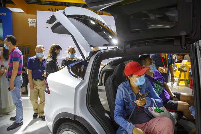 Visitors wearing face masks to protect against the coronavirus look at a Tesla Model X SUV on display at the China International Fair for Trade in Services (CIFTIS) in Beijing, Saturday, Sept. 5, 2020. China's car sales rose 6% in August over a year earlier as the industry's biggest market recovered from the coronavirus pandemic, but purchases for the year to date were off more than 15%, an industry group reported Thursday, Sept. 10, 2020. (AP Photo/Mark Schiefelbein)